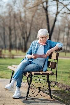 레크리에이션. 벤치에 앉아있는 동안 잡지를 읽고 결정된 금발 여자