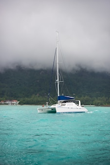 Recreational yacht in fog at the coast of seychelles.