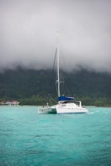 Яхта для отдыха в тумане на побережье сейшельских островов.