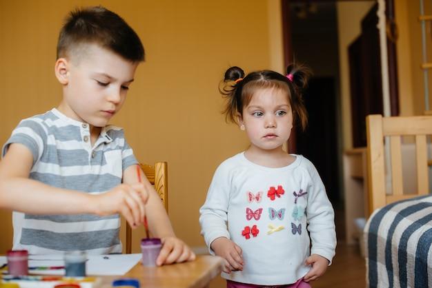 男の子と女の子が一緒に遊び、ペイントします。 recreationndエンターテイメント。家にいる。