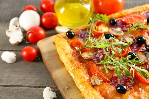 テーブルの上の長方形のおいしいピザと野菜、クローズアップ