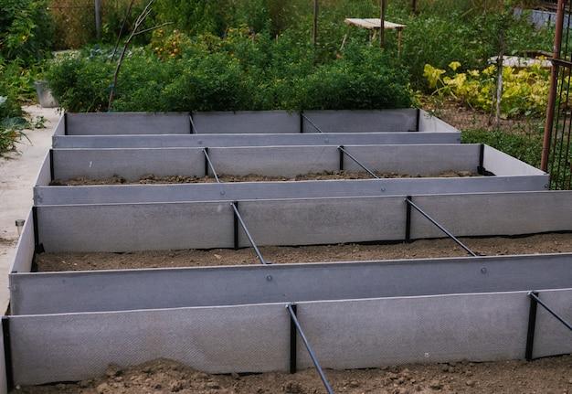 자신의 손으로 만든 정원의 직사각형 침대. 식물 심기의 편리함. 슬레이트와 금속으로 만든 침대.