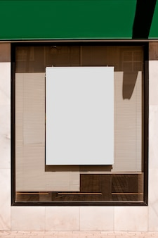 Rectangular blank billboard on glass window with blinds