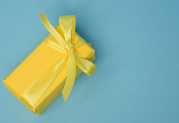 노란색 종이로 싸서 실크 노란색 리본으로 묶인 선물이있는 직사각형 상자, 평면도