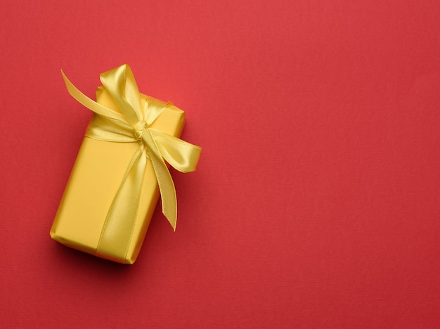 Rectangular box with a gift wrapped in yellow paper and tied with a silk yellow ribbon, top view