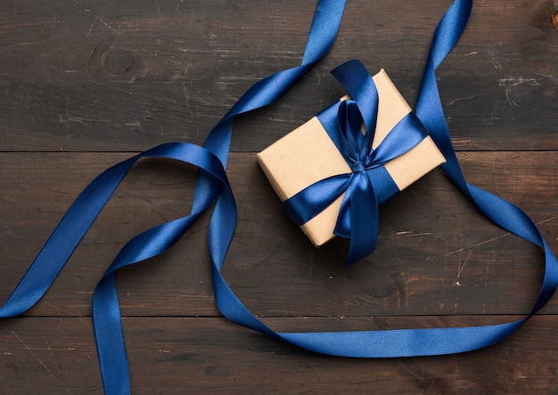 Rectangular box wrapped in brown paper and tied with a blue silk ribbon with a bow, gift on a brown wooden background, top view