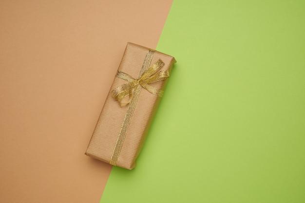 Прямоугольная коробка, обернутая в коричневую бумагу и перевязанная шелковой лентой с бантом, подарок на зеленом фоне, вид сверху, копировальное пространство