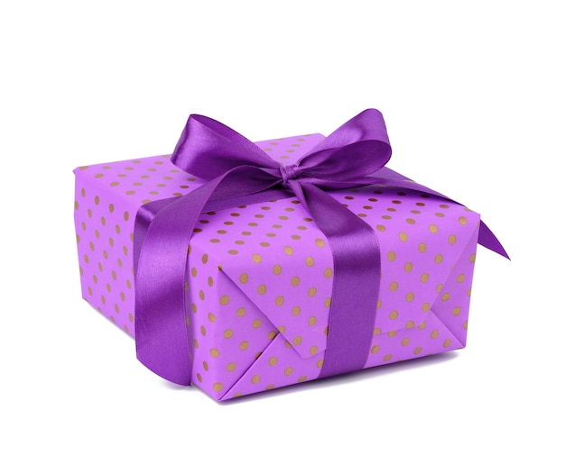 Rectangular box wrapped in purple polka dot paper and tied with a silk ribbon on a white background, celebration