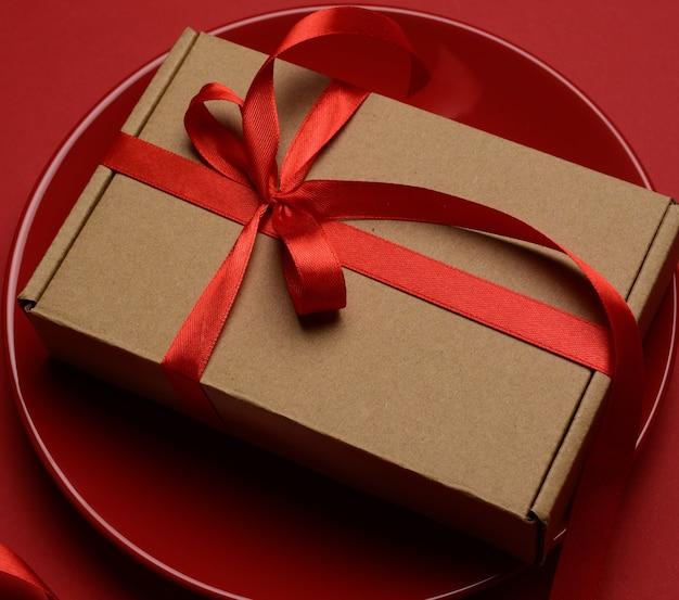 Прямоугольная коричневая картонная коробка, перевязанная красной шелковой лентой, лежит на круглой керамической красной тарелке, вид сверху