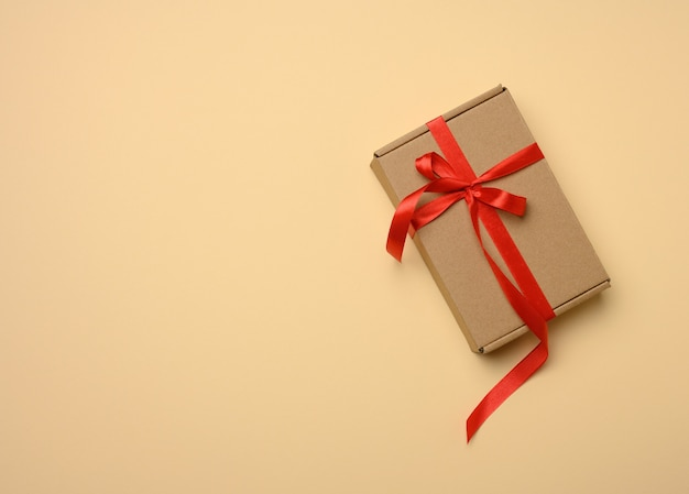 Rectangular brown cardboard box tied with a silk red ribbon on a beige background, top view, close up