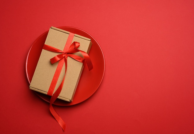 Rectangular brown cardboard box tied with a silk red ribbon lies in a round ceramic red plate, top view
