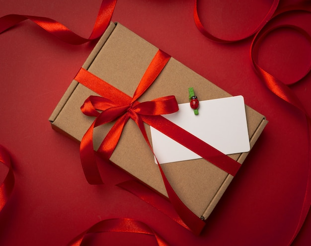 Rectangular brown cardboard box tied with a silk red ribbon on a red background, top view, close up