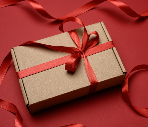 Rectangular brown cardboard box tied with a silk red ribbon