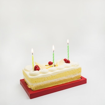 Rectangular cake with lighted candles on white background