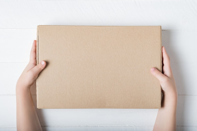 Rectangular cardboard box in children's hands. top view,