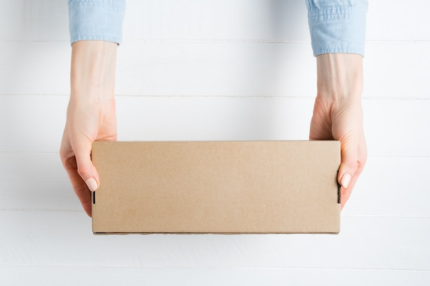 Rectangular cardboard box in female hands. top view, white surface