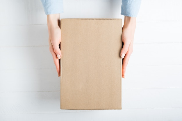 Rectangular cardboard box in female hands. top view,