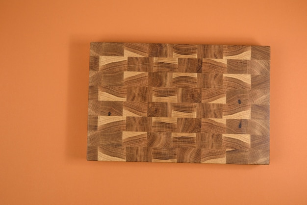 Прямоугольная пустая деревянная коричневая разделочная кухонная доска на оранжевом фоне, вид сверху