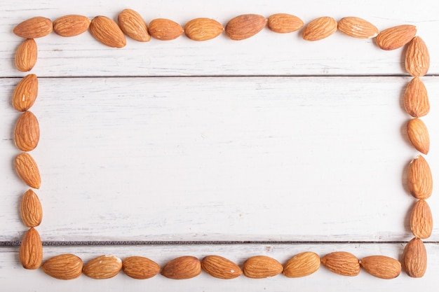 Rectangular frame made from almonds on white wooden background