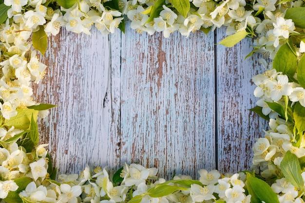 木製の青い背景に白いジャスミンの花で作られた長方形のフレーム。バックグラウンド。