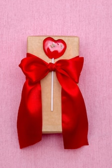 Прямоугольная подарочная коробка с красной лентой на розовом фоне