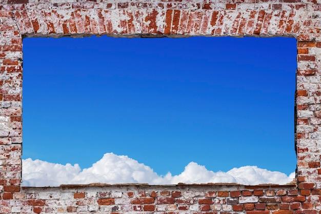 Прямоугольное отверстие в кирпичной стене с голубым небом и облаками. фото высокого качества
