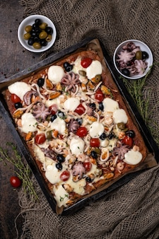 Rectangular homemade seafood pizza with octopus, shrimp, mussels and squid on a dark wooden background. close-up and top view.