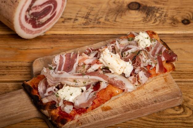 木製のテーブルに豚バラ肉のピザの長方形の自家製スライス。イタリア料理