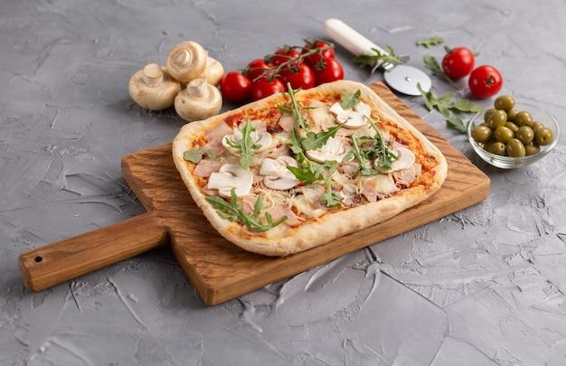 나무 커팅 보드에 버섯, 토마토, 아루굴라를 넣은 직사각형 피자