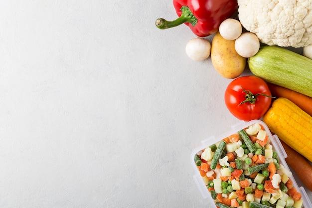 Прямоугольный пластиковый контейнер с замороженными овощами, вид сверху с копией пространства и свежими продуктами
