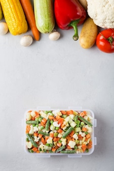 Прямоугольный пластиковый контейнер с замороженными овощами, вид сверху с местом для текста и свежих продуктов