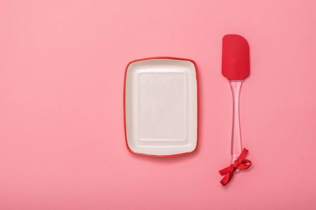 ピンクの背景に長方形のプレートとキッチンヘラ。お祝いの背景にキッチンツール。フラットレイ。