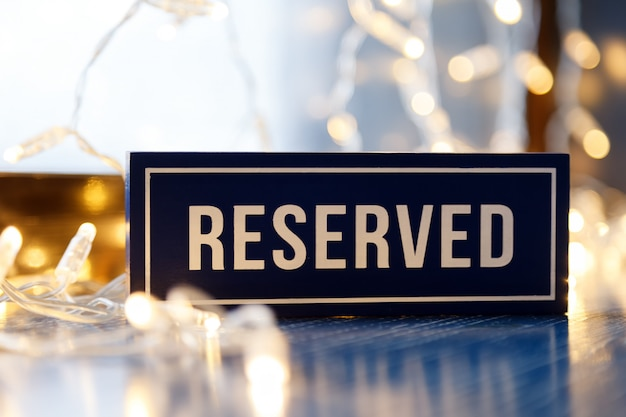 Rectangular plate with word reserved stand on table in restaurant