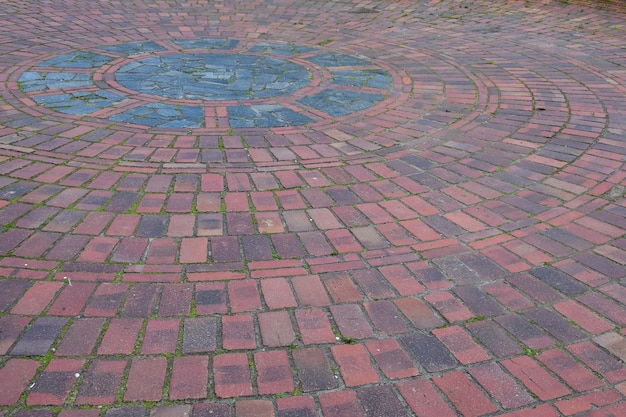 Прямоугольная уличная тротуарная плитка раскладывается по кругу в перспективе по всему кадру. центр круга смещен в верхний левый угол.