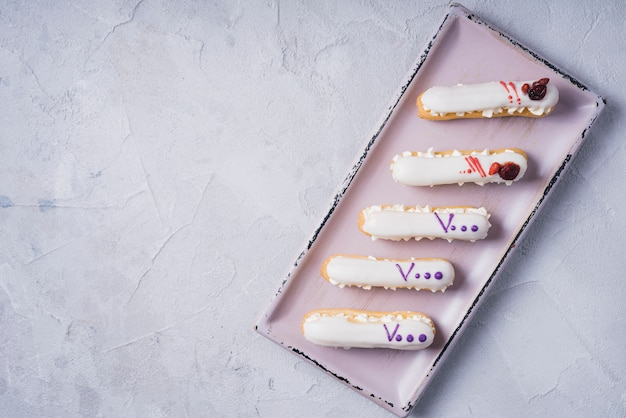 Rectangular tray with eclairs on concrete background