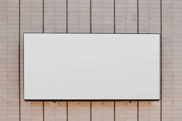 Rectangular white blank billboard on striped wall