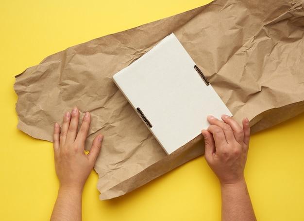 Прямоугольная белая картонная коробка и две женские руки обернуты коричневой бумагой на желтом.