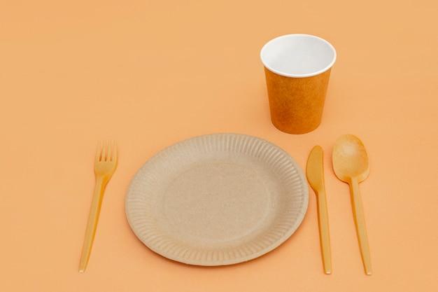 베이지색 배경에 재활용 가능한 포크, 숟가락, 칼, 접시, 컵. 주방 용품. 평면도. 미니멀리스트 스타일. 복사 공간