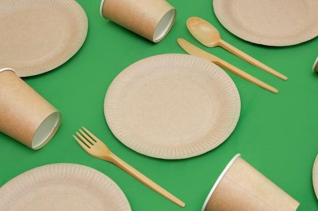 녹색 배경에 재활용 가능한 포크, 숟가락, 칼, 접시, 컵. 주방 용품은 테이블에 제공됩니다. 평면도. 미니멀리스트 스타일. 공간을 복사합니다.