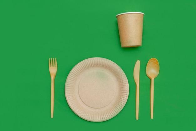 녹색 배경에 재활용 가능한 포크, 숟가락, 칼, 접시, 컵. 주방 용품. 평면도. 미니멀리스트 스타일. 복사 공간