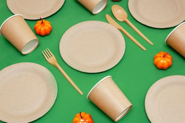 옆에 주황색 호박이 있는 녹색 배경에 재활용 가능한 포크, 스푼, 나이프, 접시, 컵. 주방 용품은 테이블에 제공됩니다. 평면도. 미니멀리스트 스타일. 복사 공간