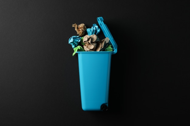 Recycle bin with trash on black background, space for text