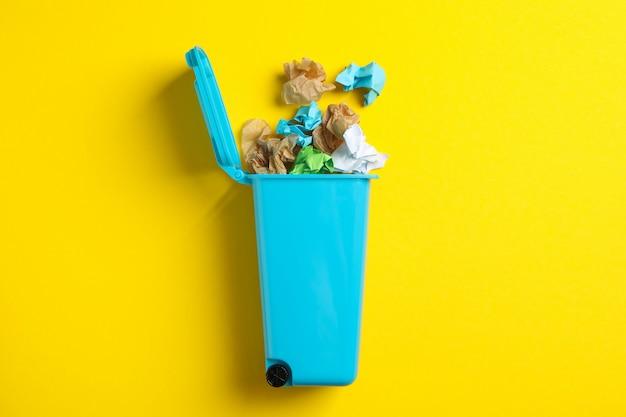 Корзина с мусором на желтом фоне, место для текста