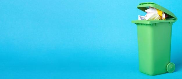 青い背景のごみ箱。プラスチック容器に入った紙。廃棄物のリサイクル。環境の概念。青い背景の上の紙のバスケット