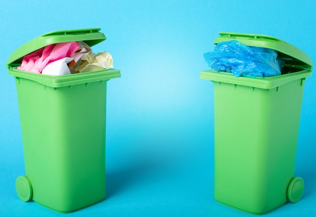 青い背景のごみ箱。紙とポリエチレン。廃棄物のリサイクル。生態学的概念。青い背景にプラスチックと紙の2つのごみ箱