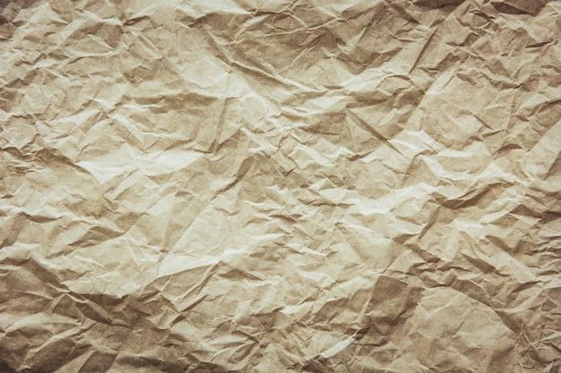 背景の茶色のしわくちゃの紙のテクスチャをリサイクルします