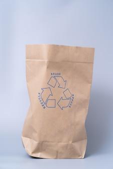 Утилизируйте коричневый бумажный пакет на сером