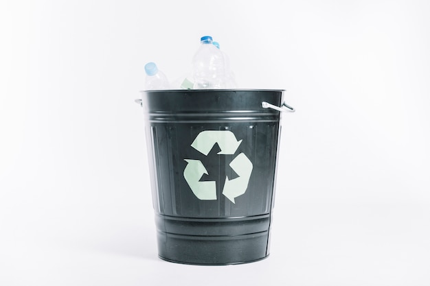 Рециркулируйте ведро с пластиковыми бутылками на белом фоне