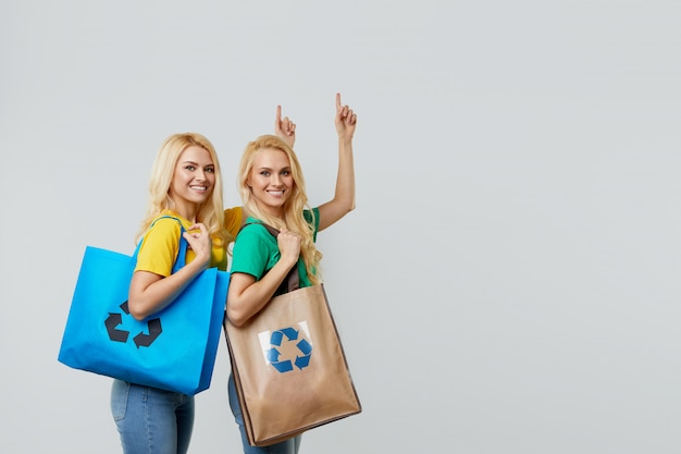 Recycle concept. young women in casual clothes are holding ecological recycled grocery bags and point up to empty space for text.