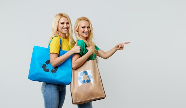 Концепция молодые женщины в повседневной одежде держат экологические переработанные продуктовые сумки и указывают на право освободить место для текста.